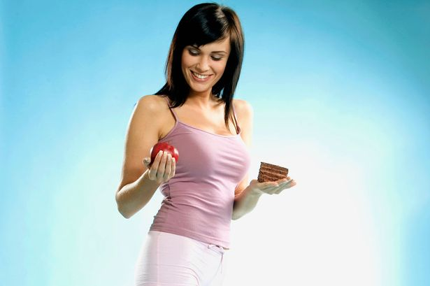 Young woman standing on scales with piece of cake and apple